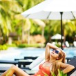 Young beautiful woman outdoors sitting on the chair near swimming-pool — Foto de Stock