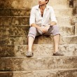 Handsome man sitting on the stairs, Bali - Stock Photo
