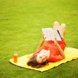 Young woman on the grass with book and orange juice — Stock Photo