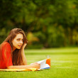 Young woman on the grass with book and orange juice — Stock Photo #19926881