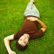 Young man on the green grass — Stock fotografie