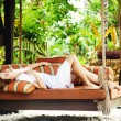 Young beautiful woman on the outdoors bed in balinese resort — Stock Photo
