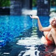 Young woman in the pool in luxury resort, Bali, Indonesia - Stock Photo