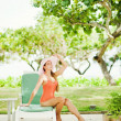 Young woman sitting on the sunbed under tree — Stock Photo