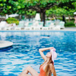 Young beautiful woman sitting near swimming pool — Stock Photo