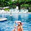 Young beautiful woman sitting near swimming pool — Foto Stock