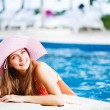 Young beautiful woman outdoors looks outside the swimming pool — Stock Photo
