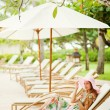 Young beautiful woman outdoors on the sunbed under umbrella - Stock Photo