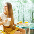 Beautiful young woman eating breakfast (soft focus) — Stok fotoğraf #19927565