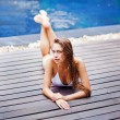 Young woman in swimsuit lying on the wooden floor outdoors — Foto de Stock