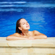 Young beautiful woman with pleasure in swimming pool in sunny day — Stock Photo