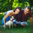 Young couple with dog on picnic in park — Foto de Stock