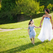 Mother and daughter walking in park — Stock Photo
