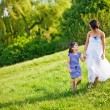 Foto Stock: Mother and daughter walking in park