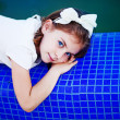 Foto Stock: Little girl near swimming pool
