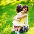 Beautiful young mother and her daughter having fun on the green grass — Stock Photo #19928223