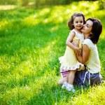 vacker ung mamma och hennes dotter att ha kul på det gröna gräset — Stockfoto #19928227