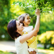 Mother with daughter in garden — Stock Photo #19928235