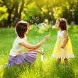 Happy young mother and her daughter blowing soap bubbles in park — Stock Photo #19928257