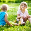 Two children are sitting on green meadow and smile — Stock Photo