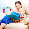 Mother  with a child reading a book — Stock Photo