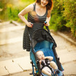 Happy young mother with baby in buggy walking in park - Stock Photo