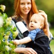 Mother carrying son in sling in park — Stock Photo