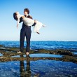 Man holds his bride on the hands - Stock Photo