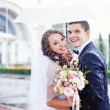 Wedding kiss in the rain - Stock Photo