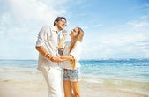 Couple talking by phone on beach — Stock Photo