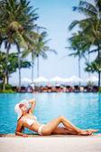 Joven hermosa mujer sentada junto a la piscina — Foto de Stock