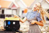 Caucasian woman with gasoline powered generator outdoors — Stock Photo