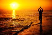 Kadın yoga gün batımında sahil üzerinde uygulamak — Stok fotoğraf