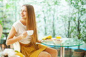 Beautiful young woman eating breakfast (soft focus) — Stock Photo
