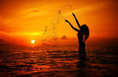 Long hair woman silhouette in the sea splashing water — Stock Photo
