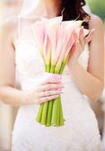 Bride holding beautiful wedding bouquet — Stock Photo