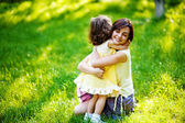 Beautiful young mother and her daughter having fun on the green grass — Foto de Stock