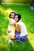 Beautiful young mother and her daughter having fun on the green grass — Stock Photo