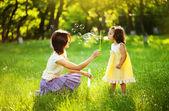 Feliz jovem mãe e sua filha soprando bolhas de sabão no parque — Foto Stock