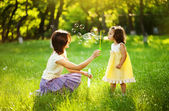 Happy young mother and her daughter blowing soap bubbles in park — Stock Photo