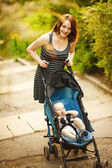 Happy young mother with baby in buggy walking in park — Foto de Stock