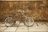 An old, rusty white bicycle leaning against a grungy wall in bali — Foto Stock