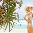 Woman near palms on tropical beach — Stock Photo #25560471