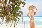 Woman near palms on tropical beach — Stock Photo