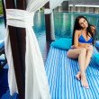Beautiful woman relaxing on lounger in hotel, bali — Stock Photo #26365889