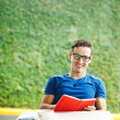 Young man reading a red book at home — Stock Photo