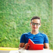 Foto Stock: Young man reading a red book at home