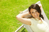 Woman relaxing on lounger in the garden — Stock Photo