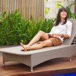 Pretty brunette womrelaxing on lounger outdoors — Stock Photo #30761743