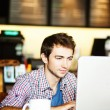Serious man with laptop in cafe — Stock Photo